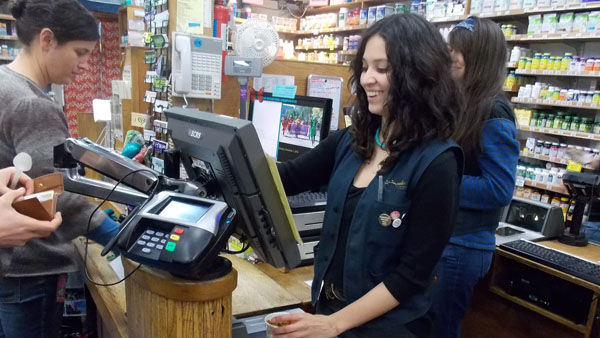 Sundance Natural Foods Manager Tera Ponce rings up a customer for a hot cup of soup with a big smile on her face. Being a cashier is just one of the many roles she plays while running the store.